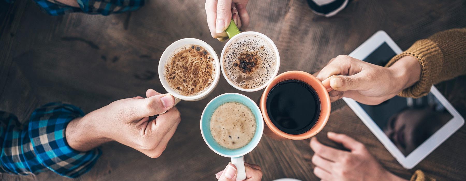 Friends toasting their coffee mugs